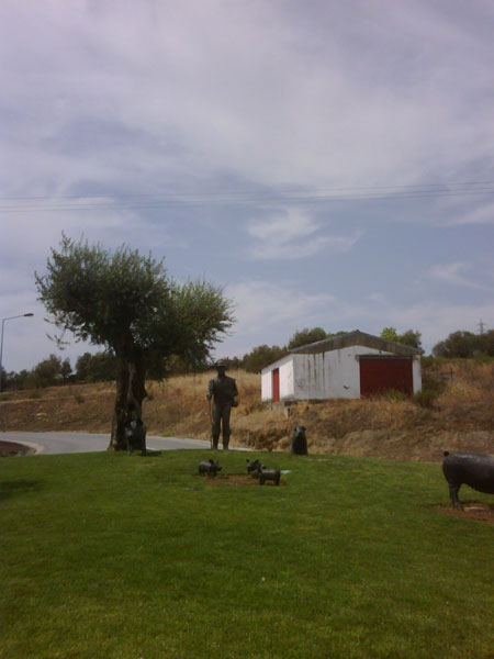 Pig man, pigs and piglets on Portuguese roundabout
