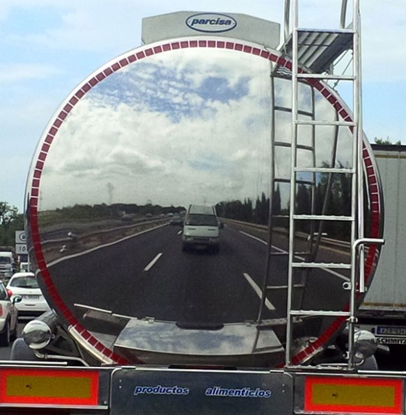 Stuck behind a very shiny tanker, the Animalcouriers van looks like it's coming through a porthole!