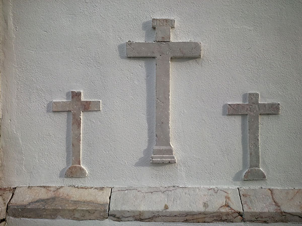 Symbols of the crucifixion on the side wall of the monastery