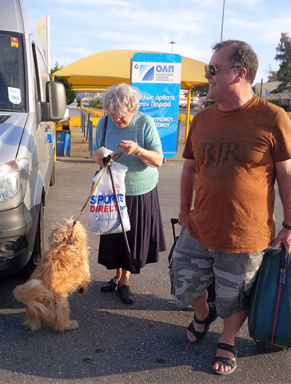 Heading towards the ferry to Crete, courier Mike helps with the luggage while Booby clamours for Freya's attention