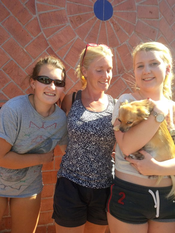 Lola getting big hugs from her owner Emma (R), with Mum Jo in the middle and sister Katie (L). Happy Lola dashed about, saying, hello! and, I'm home! to one after the other.