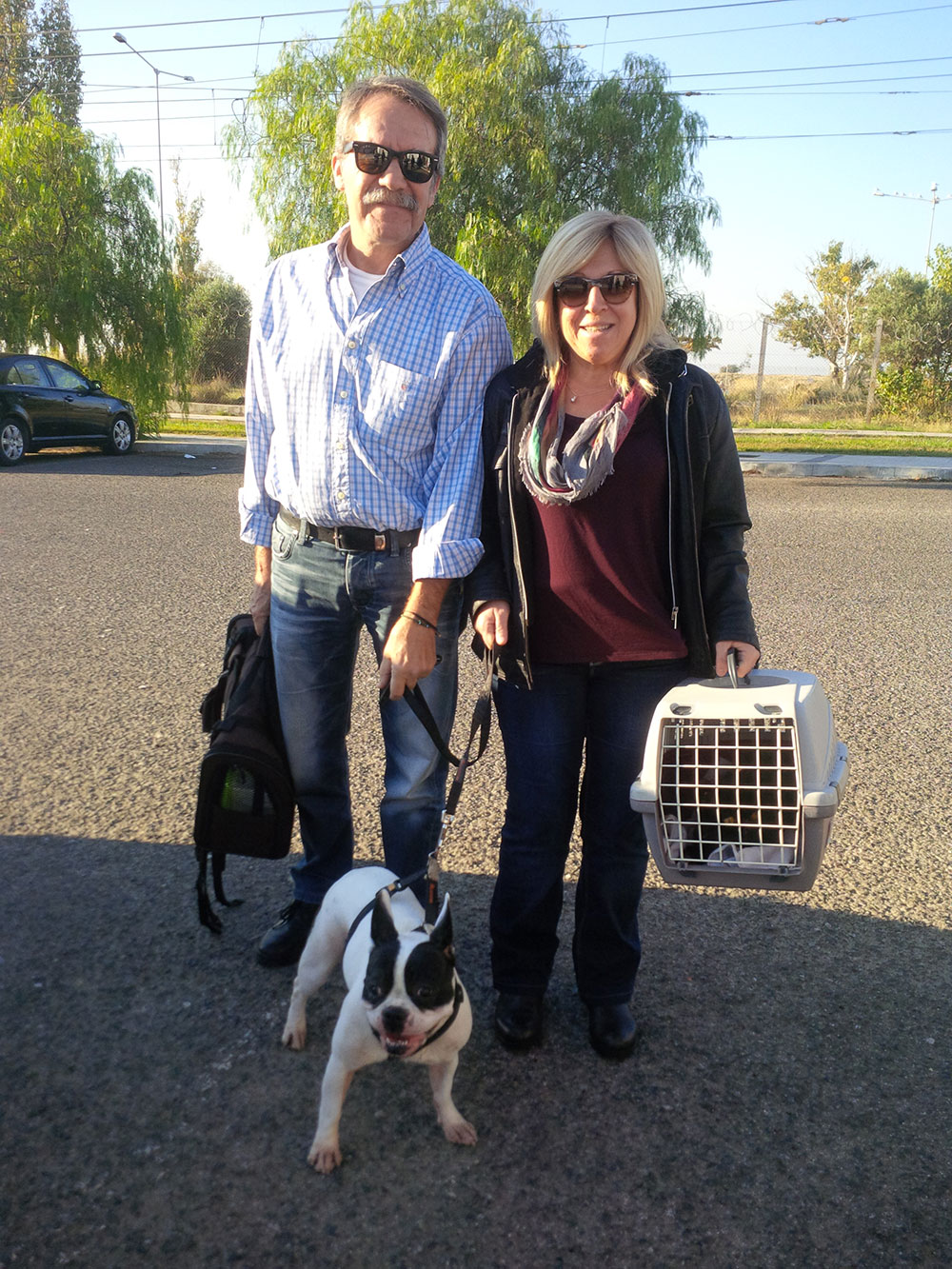 Toula and Zisis with their dog Zoe — in the cat box is Gismo, who belongs to their daughter Sophia