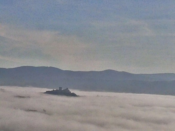 A castle poking its head out of the mist